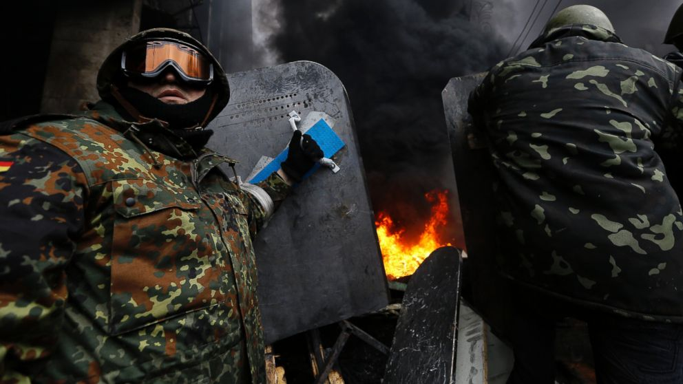 PHOTO: Anti-government protesters prepare to advance over a burning barricade in Kievs Independence Square, Feb. 20, 2014.