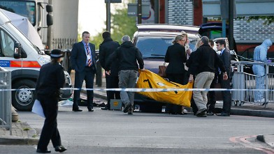 Police officers carry equipment while investigating a crime scene of an apparent attack that left one man confirmed dead and two people wounded near Woolwich barracks in London, May 22, 2013.