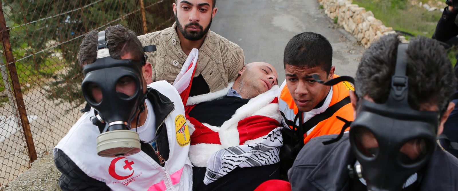 PHOTO: A Palestinian protester dressed in a Santa Claus costume is carried by medics after inhaling tear gas fired by Israeli troops during a demonstration near a Bethlehem checkpoint.