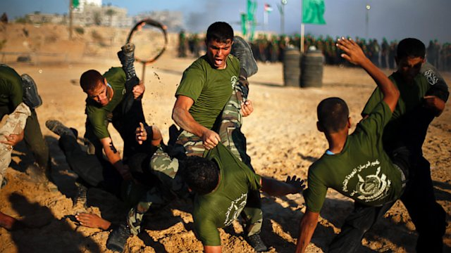 Young Palestinians take part in a military-style graduation ceremony run by Hamas, during a scouting summer camp next to the border between Egypt and Rafah, southern Gaza Strip, June 19, 2013.