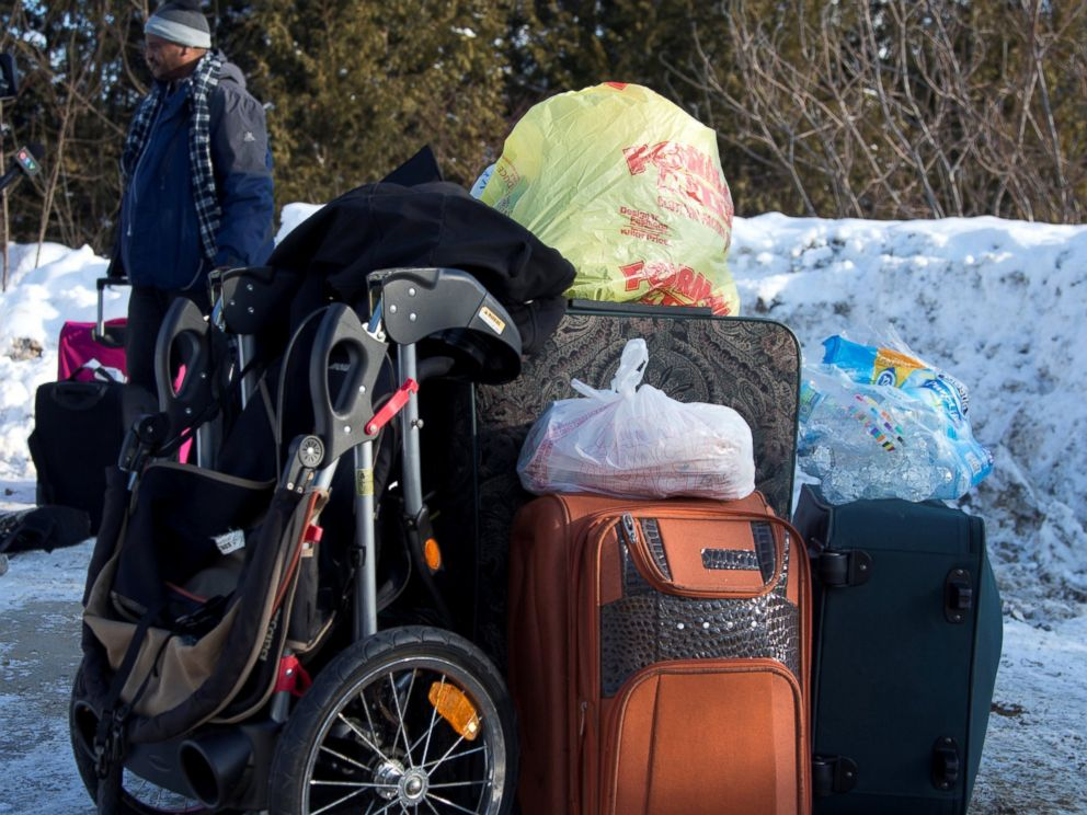 PHOTO: A man claiming to be from Sudan is detained with his familys luggage by a U.S. border patrol officer after his family crossed the U.S.-Canada border into Hemmingford, Canada, from Champlain in New York, Feb. 17, 2017.
