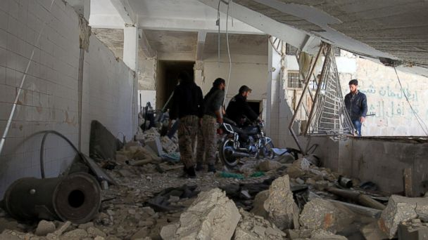 PHOTO: Men salvage a motorbike amid the damage inside a medical point at a site hit by airstrikes on Tuesday, in the town of Khan Sheikhoun in rebel-held Idlib, Syria April 5, 2017.