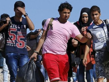 PHOTO: Syrian migrants walk to the shore to board a dinghy bound for the Greek island of Lesbos, in the Turkish coastal town of Behramkale, in Canakkale province, Turkey, Aug. 27, 2015.