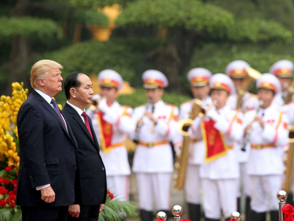 PHOTO: President Donald Trump, accompanied by Vietnamese President Tran Dai Quang, observe the playing of national anthems during a welcoming ceremony at the Presidential Palace in Hanoi, Nov. 12, 2017.