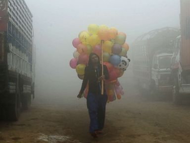 photo a pakistani vendor carries balloons on a street amid heavy smog in lahore