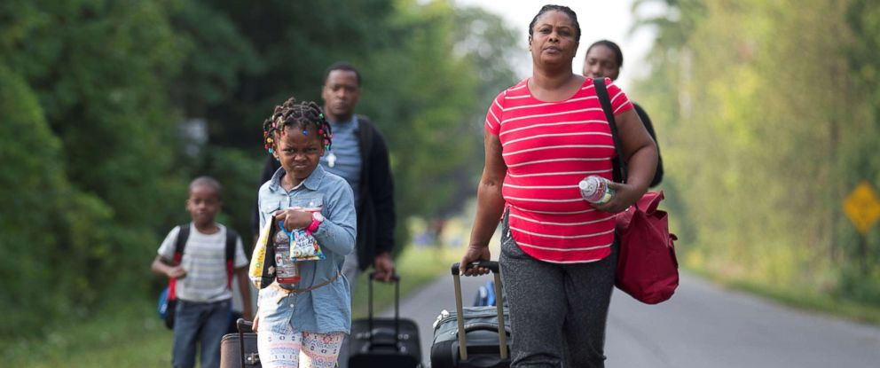 PHOTO: A family that stated they are from Haiti walk to the US-Canada border to cross into Canada from Champlain, New York, Aug. 11, 2017.