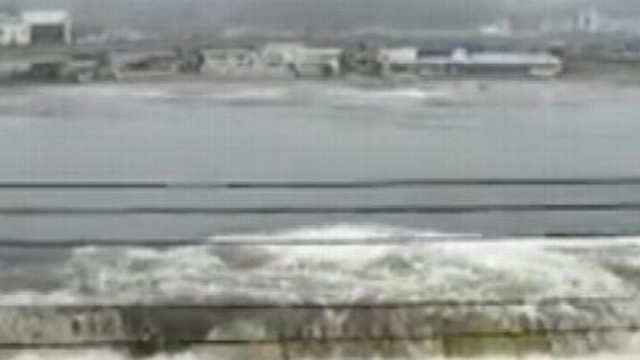 VIDEO: Watch as the powerful wave breaches floodgates, washing away a car.
