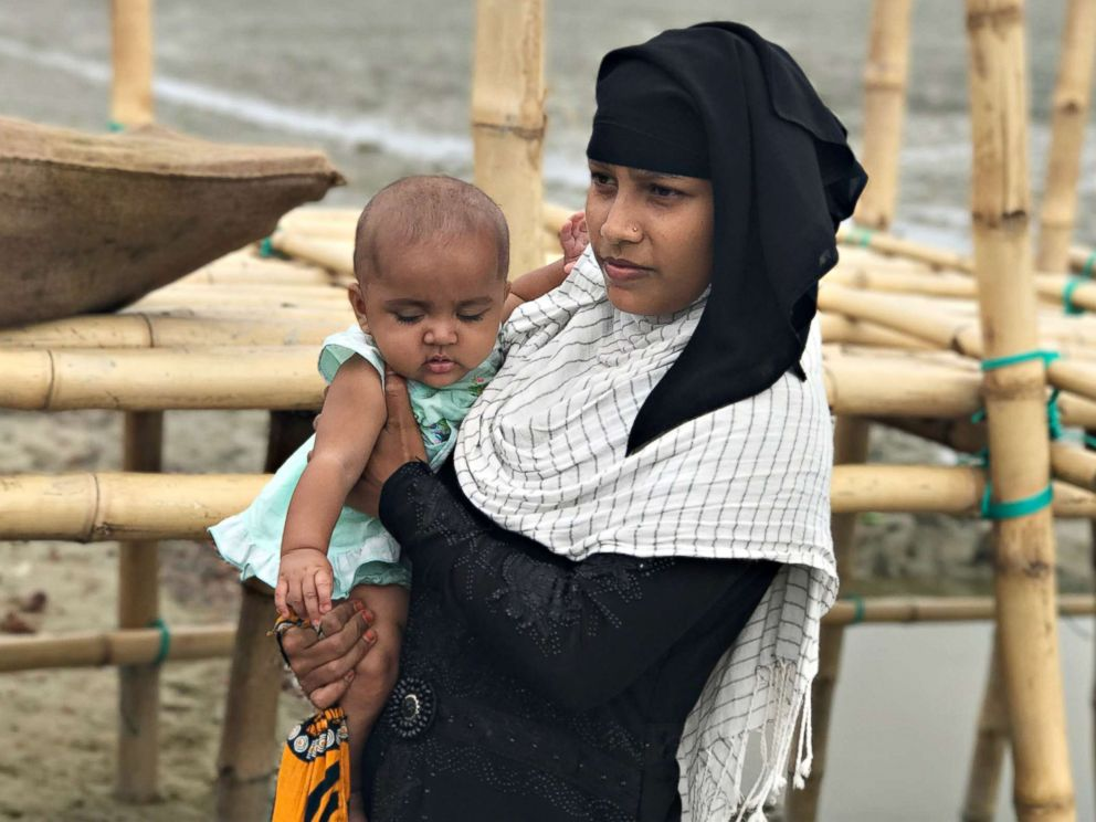 PHOTO: A Rohingya woman and her baby arrive at Shah Porir Dwip Island in Bangladesh, Oct. 2017. Once, refugees arrive, they must wait to be processed and then must make their way to the camps, which are several miles away.