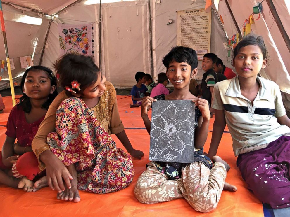 PHOTO: Rohingya children show off artwork at a Save the Children site in Bangladesh.
