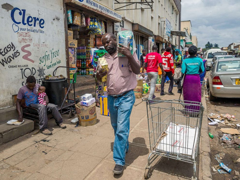 PHOTO: A man carries his wares through a market as business continues in the Zimbabwean capital Harare on Nov. 16, 2017, a day after the military announced plans to arrest criminals close to the president.