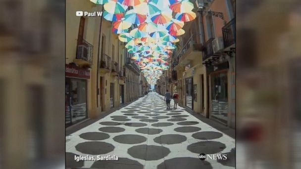 Check out this beautiful umbrella display over the streets of Iglesias in Sardinia, Italy. At noon, daily, the umbrellas project their shadows directly onto the pavement below.