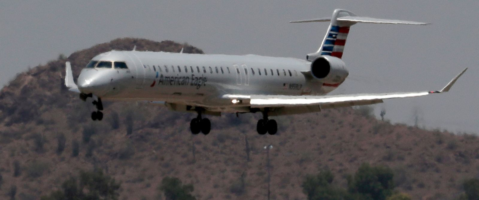 PHOTO: An American Eagle jet is seen through heat ripples as it lands at Sky Harbor International Airport, June 19, 2017, in Phoenix. American Airlines cancelled dozens flights out of Phoenix today due to extreme heat.