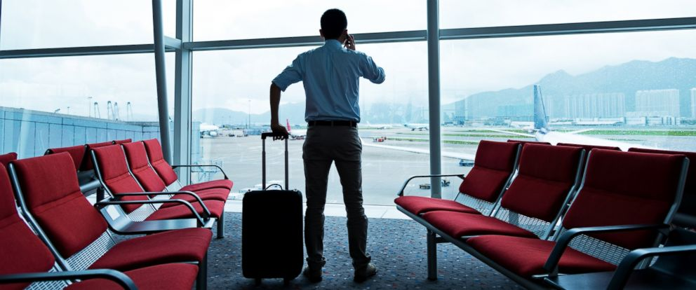 PHOTO: A traveler with luggage waiting for his flight