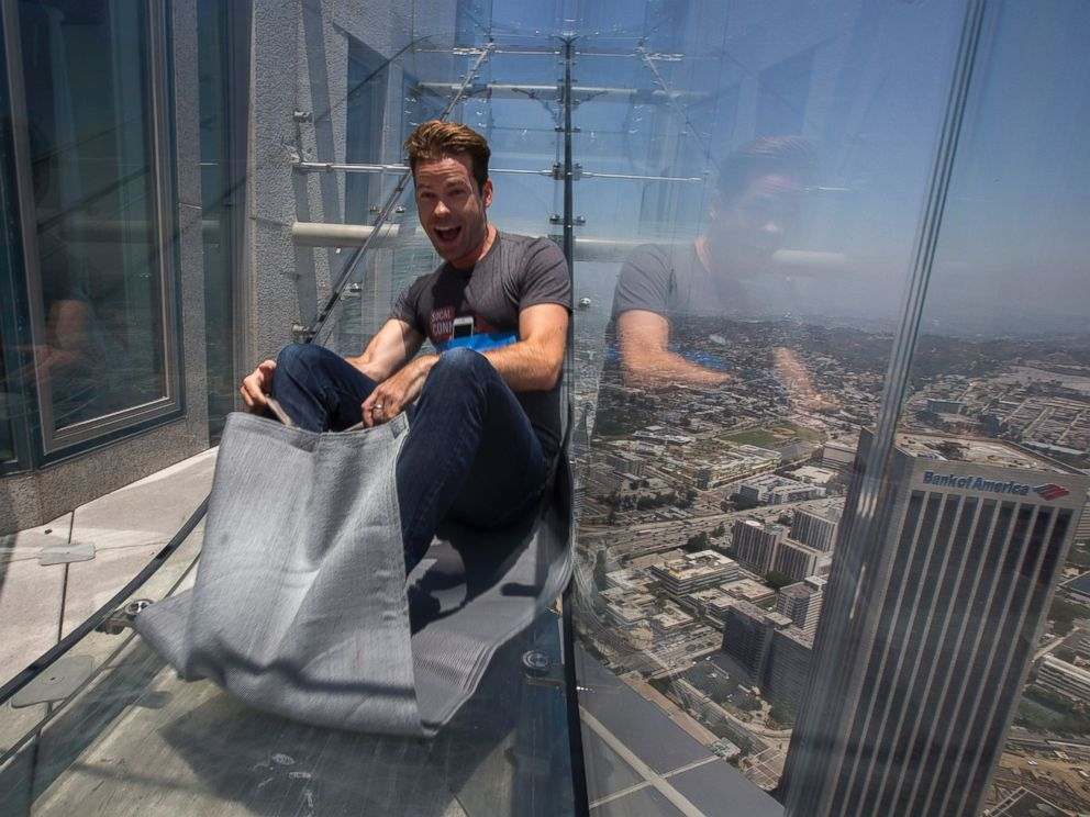 PHOTO: People slide down the Skyslide, a 45-foot (13.7-meter) glass slide 70 floors up on the outside of the US Bank Tower, on June 23, 2016 in Los Angeles, Calif.