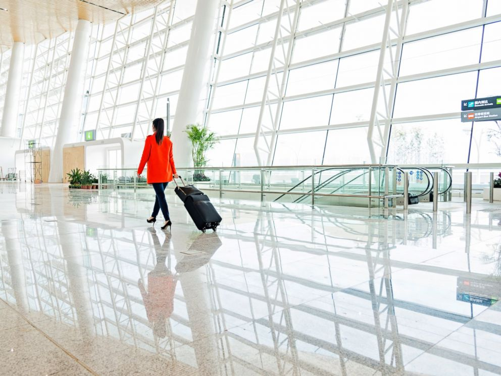 photo a young woman walks through the airport with luggage in this undated stock photo
