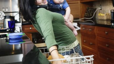 PHOTO: A busy mother holds her child while putting dishes in a dishwasher in this stock image.