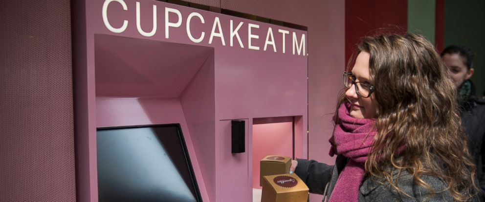"PHOTO: A woman takes her order after using the ""Cupcake ATM"" created by Sprinkles Cupcakes"