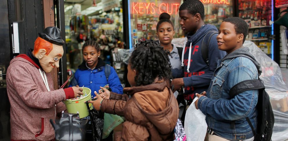 PHOTO: The proprietor of the Big Brothers Discount Hardware Store serves candy to trick or treaters on Oct. 31, 2013 in New York City.