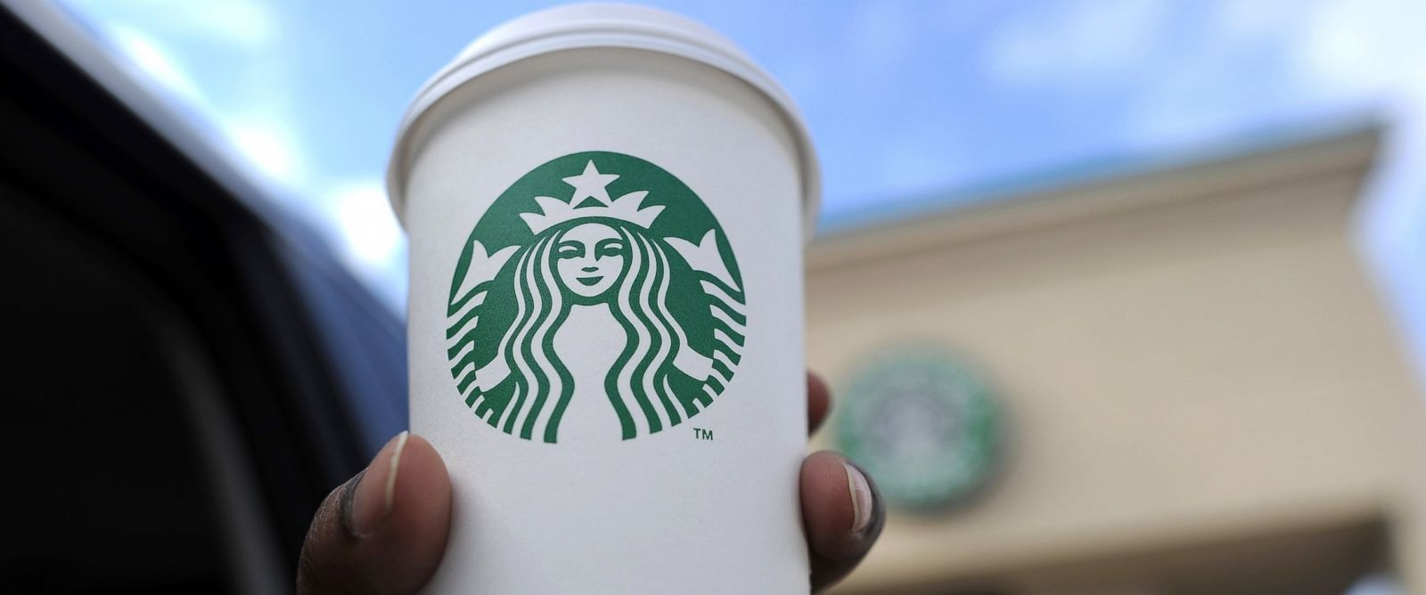 PHOTO: A woman holds up her cup in front of a Starbucks coffee shop in Silver Spring, Md., March 28. 2013.