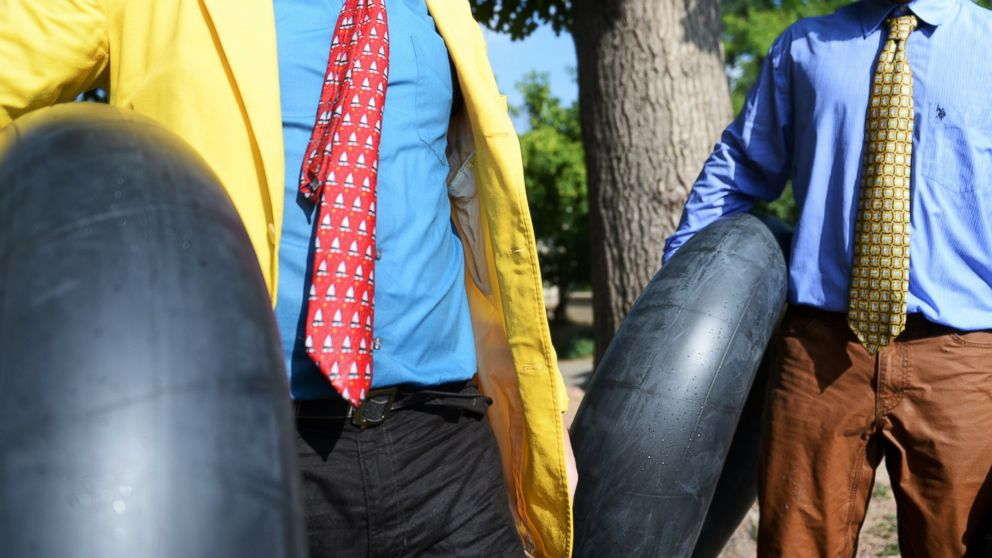 PHOTO: Tim Laramy, left, and Jack Craig dressed in ties carry their tubes as they finish riding Boulder Creek during Boulders Tube to Work Day, July 15, 2014.