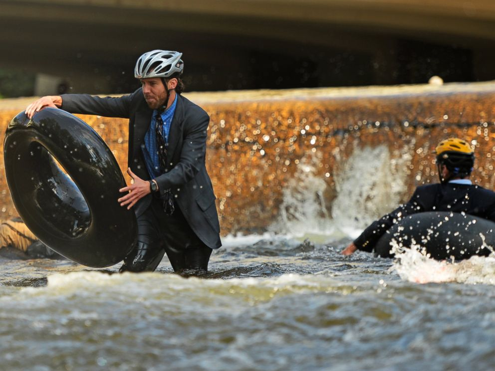 PHOTO: Quayle Hodek, dressed in a suit and tie, hops back on his tube during Boulders Tube to Work Day, July 15, 2014.
