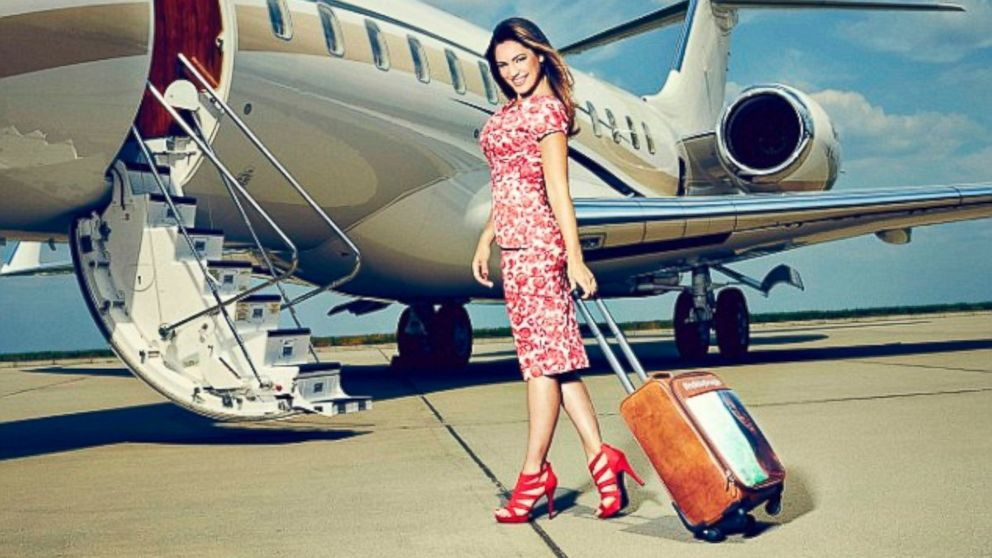 PHOTO: Model, TV personality and serial social media holiday bragger Kelly Brook shows off the worlds first selfie suitcase as she boards a plane in London.