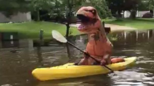 PHOTO: Travis Spry dressed as a dinosaur and kayaked through the flooded streets in Midland, Mich., June 23, 2017.