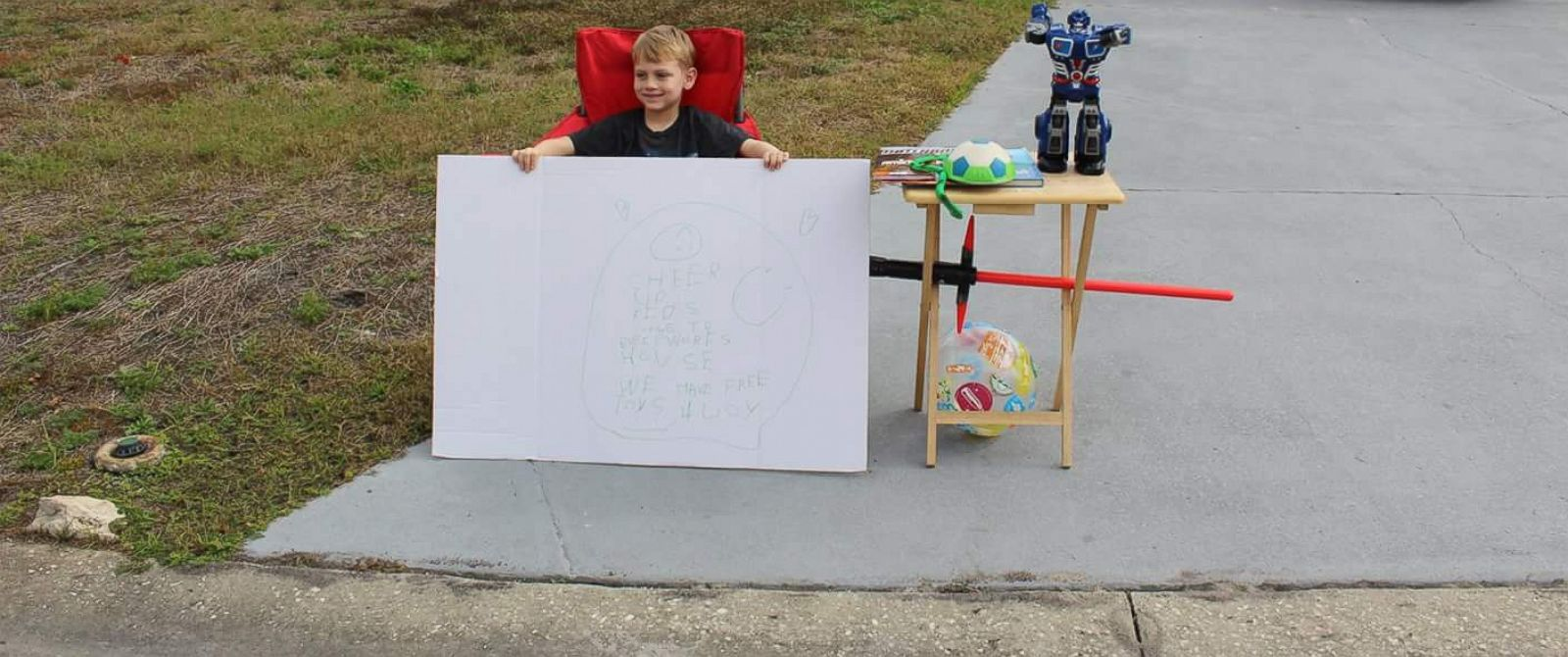 """PHOTO: Little boy, Blake Work, paid it forward by holding a """"free toy"""" stand for children who are less fortunate."""