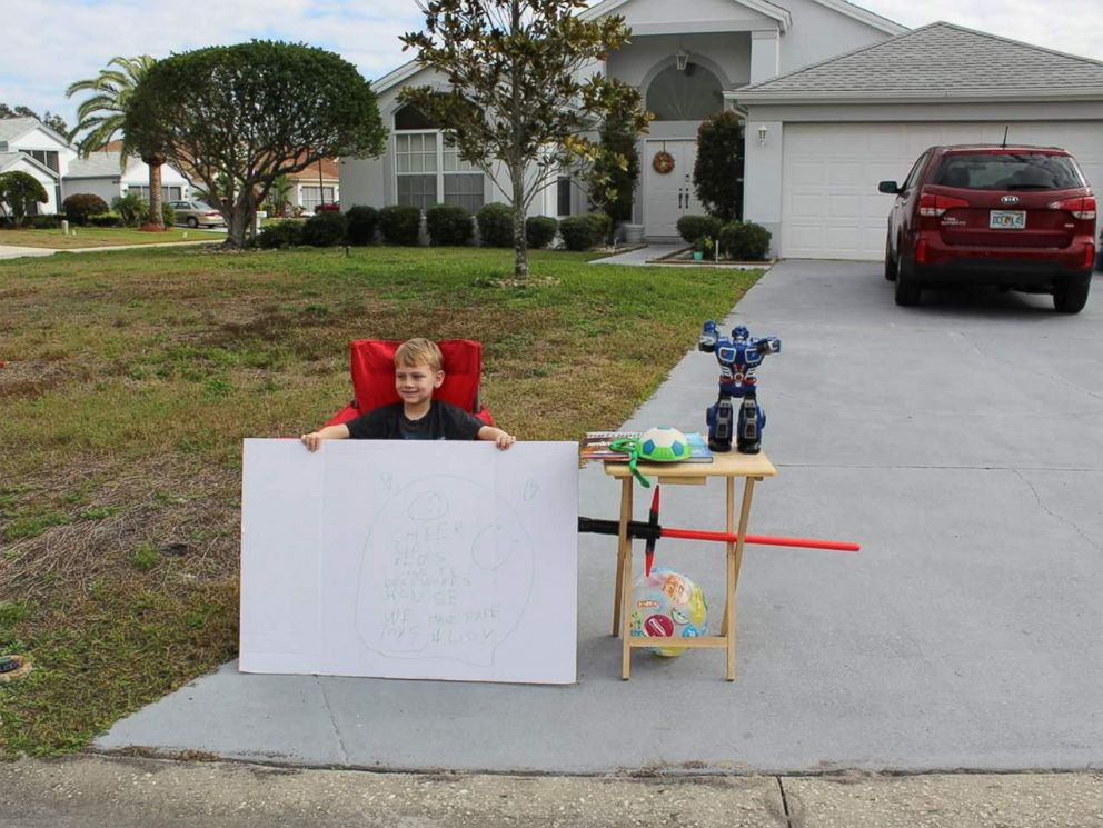 PHOTO: Little boy, Blake Work, paid it forward by holding a free toy stand for children who are less fortunate.