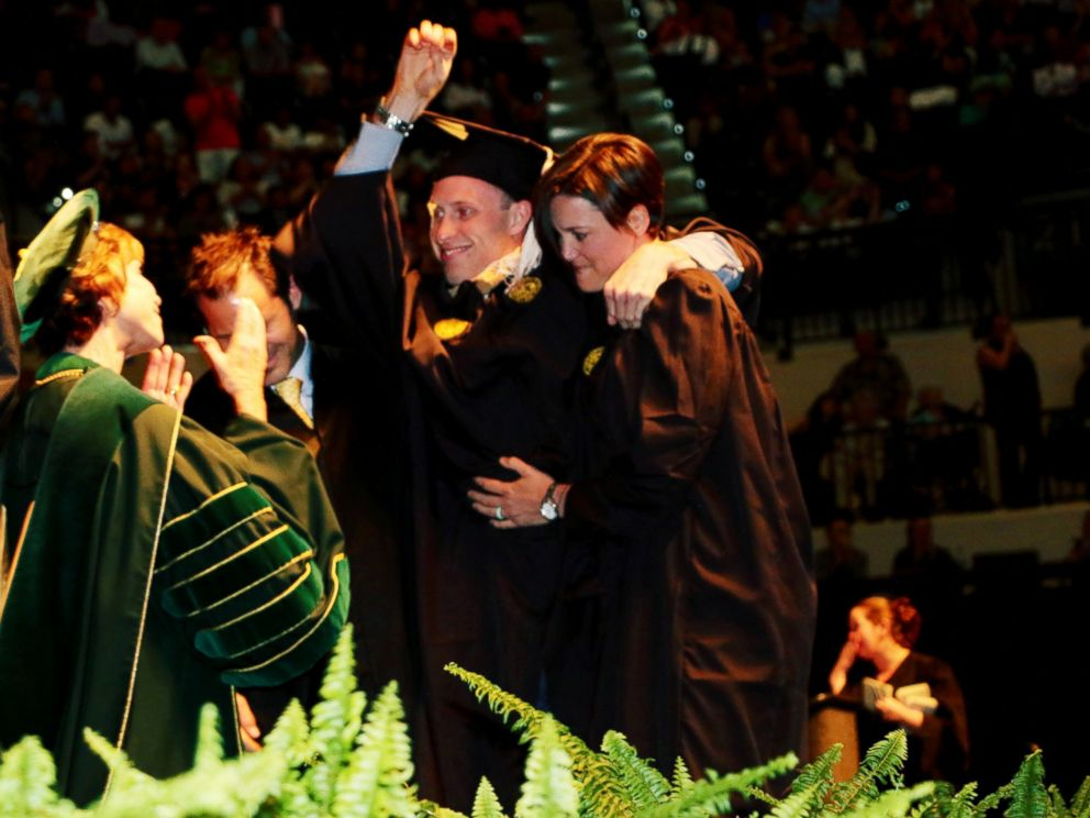 PHOTO: Sam Bridgman stood up with the help of two friends and physical trainers to walk across the graduation stage at USF, May 7, 2017.