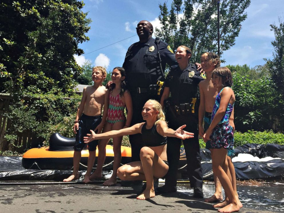 Officers jump on water slide while out on a call