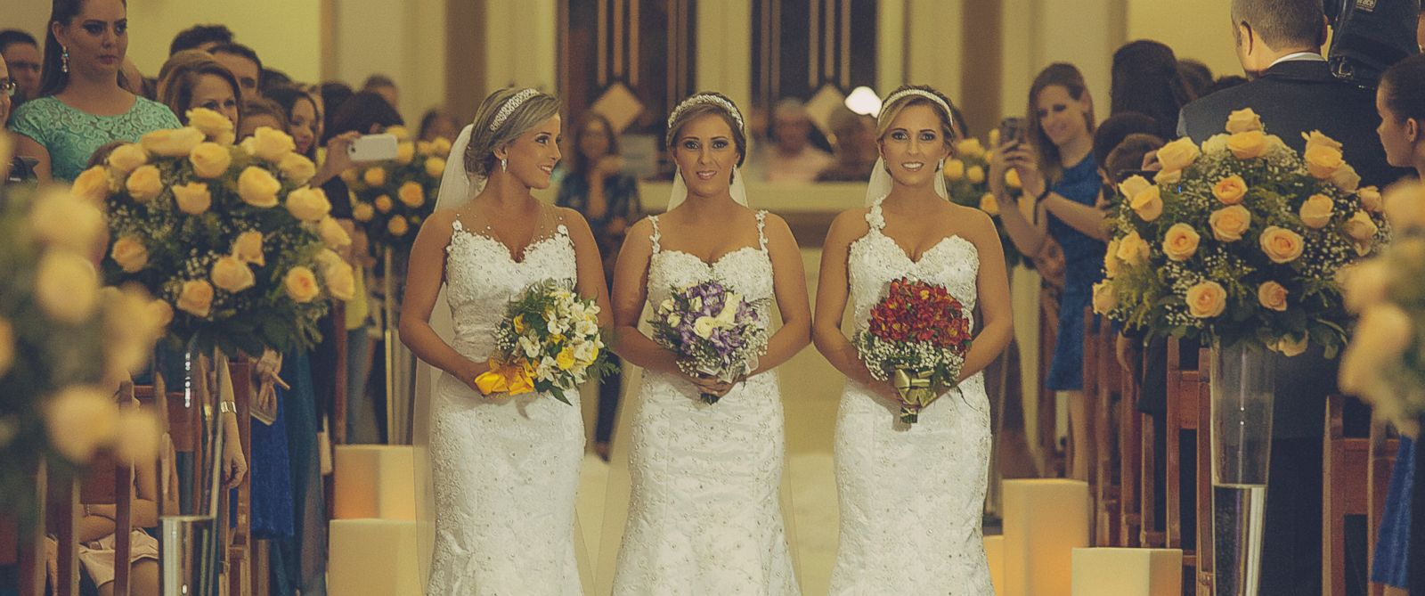 PHOTO: Identical triplets Rafaela Bini, Rocheli Bini and Tagiane Bini got married to their respective husbands together at Catedral Nossa Senhora Aparecida in Passo Fundo, Brazil, March 21, 2015.