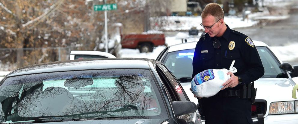 PHOTO: Billings, Montona police officer Eric Schnelbach gives a frozen turkey and a warning to Larry Riddle and his daughter Amber after they were pulled over for a minor traffic violation. Billings businessman Steve Goutanis donated the turkeys.