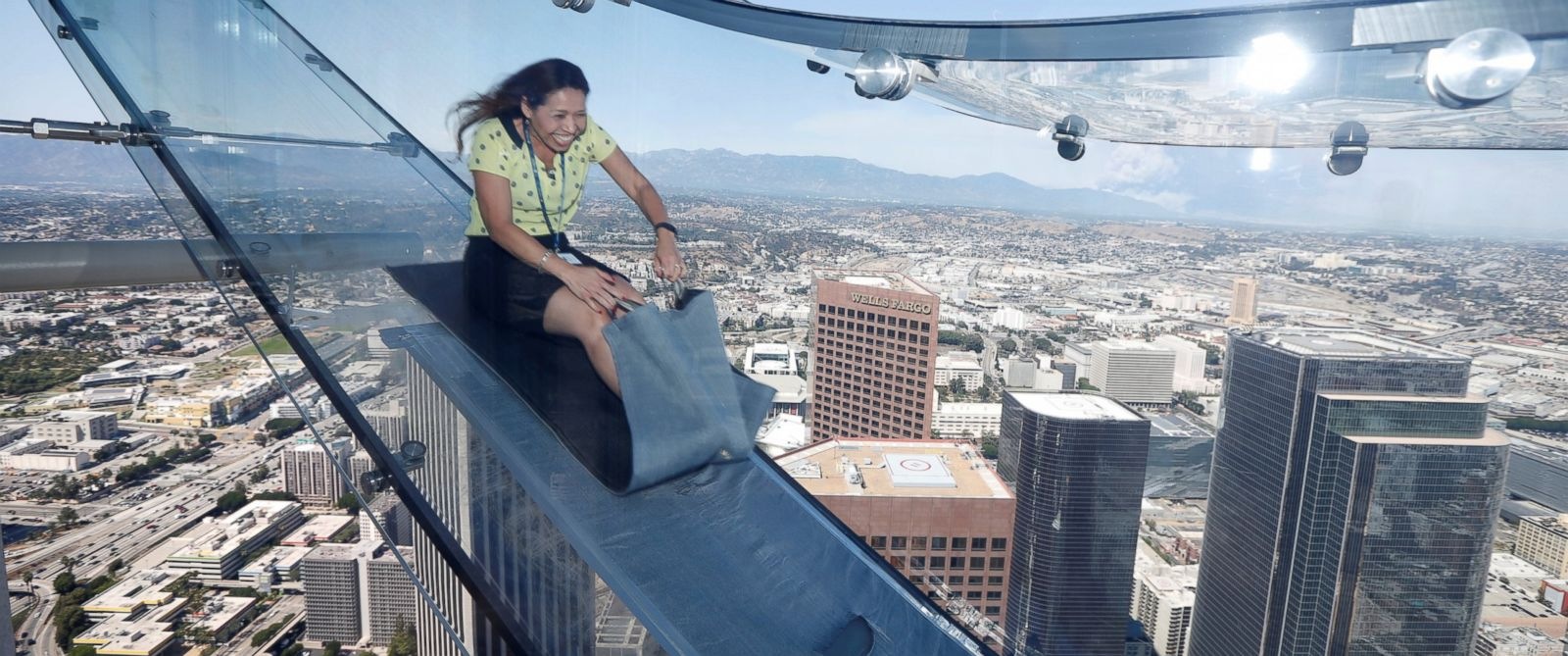 PHOTO: Sandra Brown, 40, rides the Skyslide on the 69th and 70th floors of the U.S. Bank Tower which is attached to the OUE Skyspace LA observation deck in downtown Los Angeles, California, June 20, 2016.