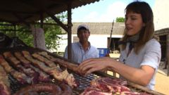 Anya Fernald, the CEO of California-based Belcampo Meat Co., looks over cuts of meat being cooked with the asado grilling technique in Uruguay.