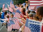 PHOTO: People wave flags as the Independence Day parade rolls down Main Street, July 4, 2014, in Eagar, Ariz.
