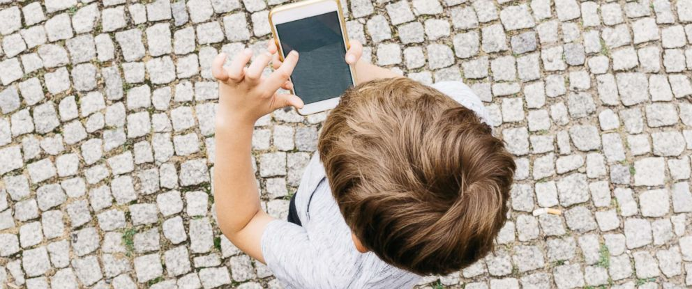 PHOTO: A child holds a smartphone in this undated stock photo.