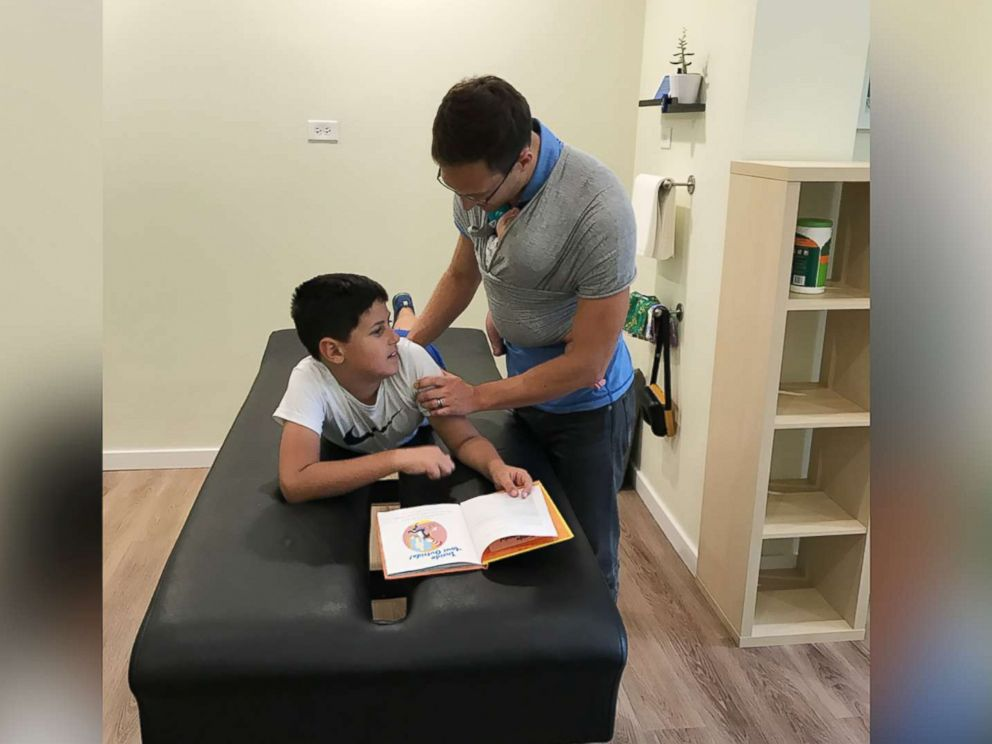 PHOTO: Yanni Rackos, 9, a patient of Roots Family Chiropractic in Chicago, Illinois, is examined by Dr. Tom Williams on July 12.