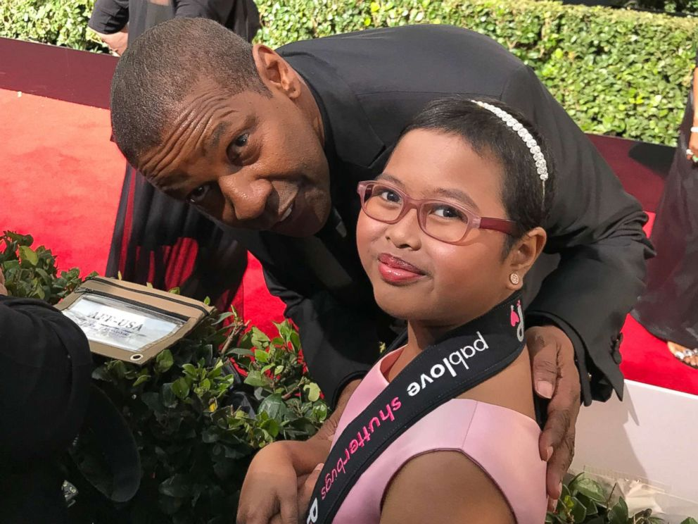 PHOTO: Francine Gascon, 10, poses with Denzel Washington as she takes photos of stars on the Golden Globes red carpet.