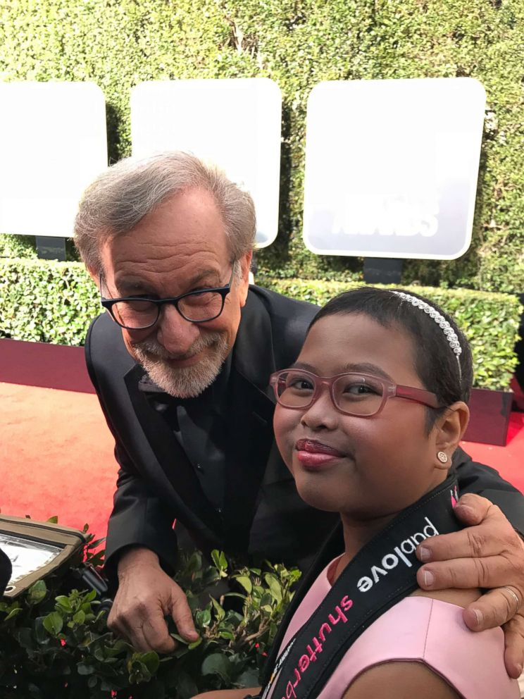 PHOTO: Francine Gascon, 10, poses with director Steven Spielberg as she takes photos of stars on the Golden Globes red carpet.