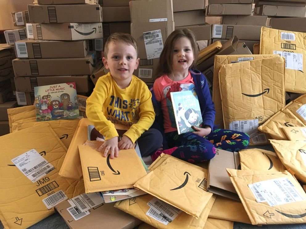 PHOTO: Lena and her twin brother Clark opening packages filled with books.