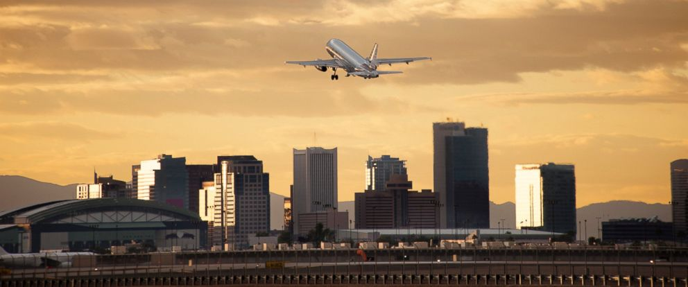 PHOTO: Airplane taking off with city skyline in background.