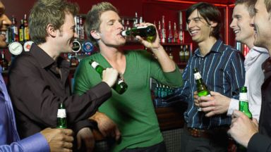 PHOTO: Men drinking bottles of beer at a bar.