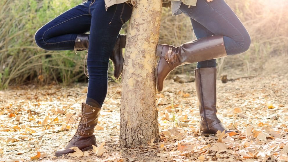 PHOTO: Two women wearing boots stand in autumn leaves.