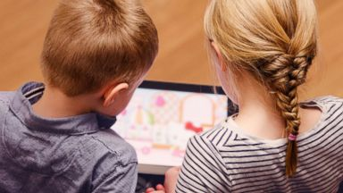 PHOTO: Two kids can be seen playing on an iPad in this stock image.