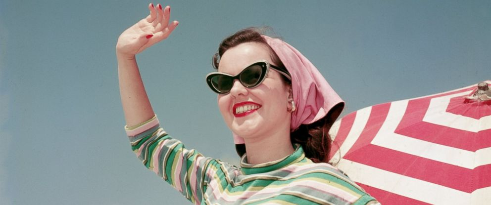 PHOTO: Vintage sunglasses are making a comeback for the summer season. Seen here, a model waves on the beach, circa 1956.