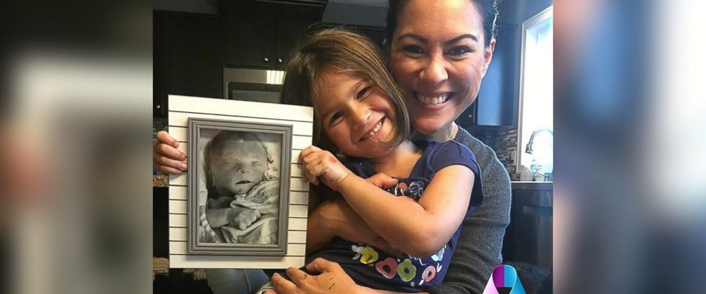 PHOTO: Anita Miron poses with her daughter, Scarlett, and a photo of her son who died at 32 weeks gestation.