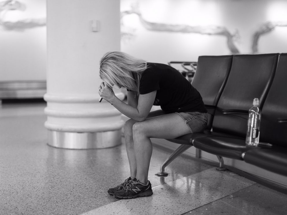 PHOTO: Sarah Lynn Olson anxiously waits out a flight delay as she and her husband David wait to board a flight to meet their daughter.
