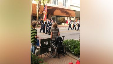 PHOTO: Arek Trenholm is wheelchair-bound but hoisted himself up to stand for the American flag.