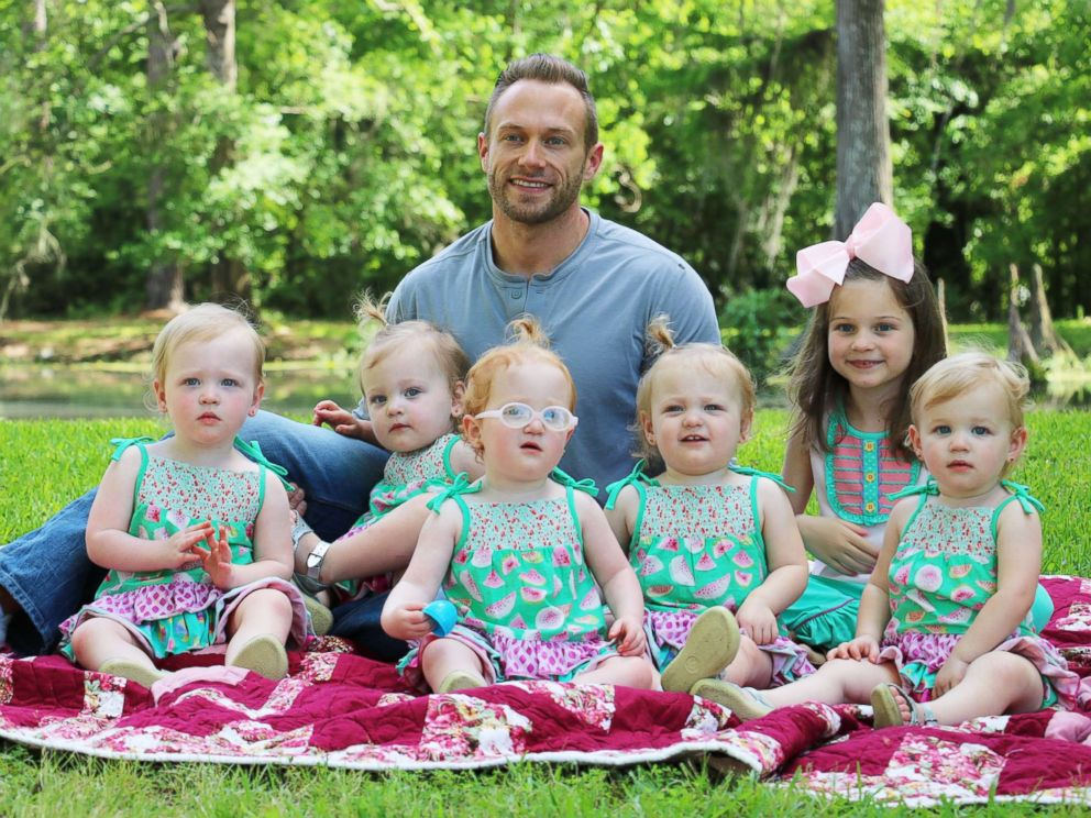 PHOTO: Adam Busby sits with his six daughters in a promotional image from the TLC show, OutDaughtered.
